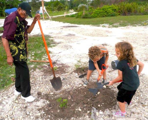 Bernando plants a tree with his great-grandchildren.